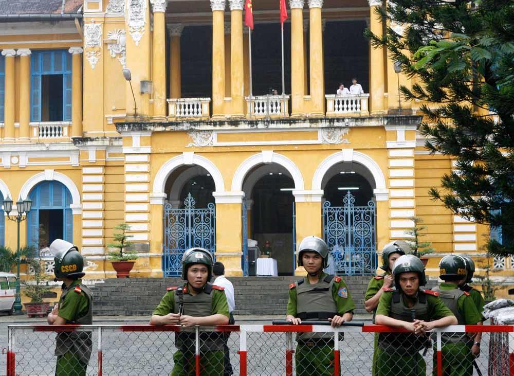 Politiemensen voor het gerechtsgebouw in Ho Chi Minhstad waar blogger Dinh Cong Le werd veroordeeld tot vijf jaar cel. – © Reuters