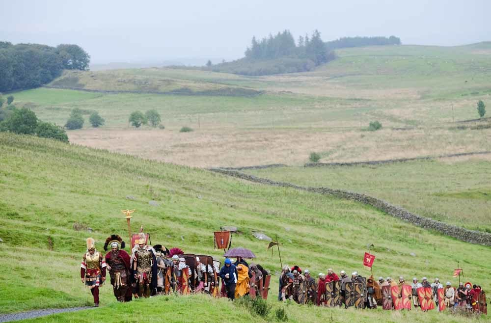 Acteurs kruipen in de rol van Romeinse soldaten tijdens een herdenking van de Muur van Hadrianus in 2016. De 117 kilometer lange muur werd tussen 122 en 128 na Chr. gebouwd om de Romeinse noordgrens te beschermen. – © Ian Forsyth / Getty