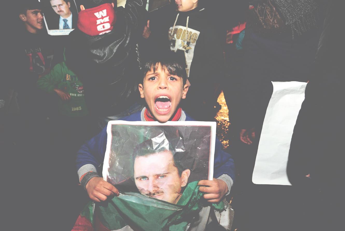 Een jongen met een poster van de Syrische president Assad. – © HH