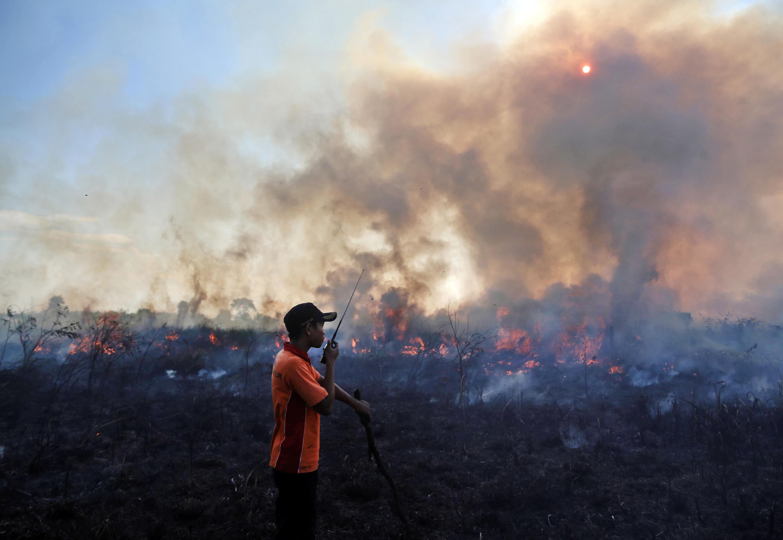 Een brand in een veengebied in Pemulutan, Zuid-Sumatra, in 2015. Hier wordt nog ouderwets gecommuniceerd met de walkietalkie. – © AP Photo