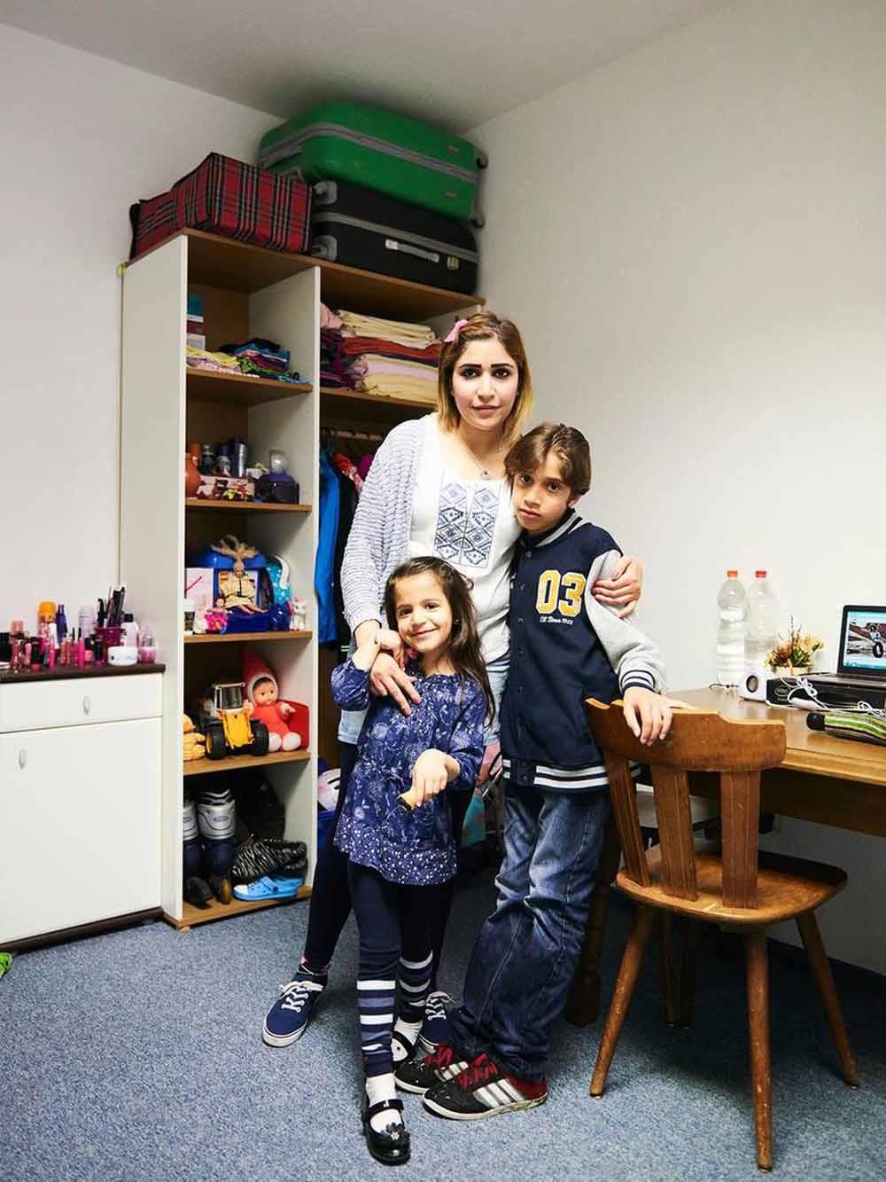 Nahed Asker met haar dochter Tala en haar zoon Said in hun woning in Wenen. Asker verloor haar man in de koelwagen. – © Philipp Horak