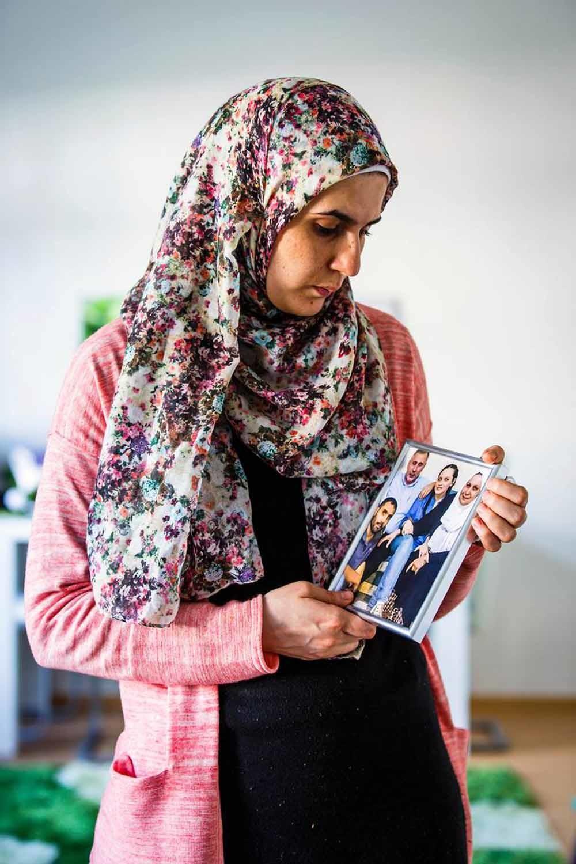 Farah Alshaikh kijkt naar een foto van haar familie. Ze verloor haar ouders, broer en zus, en kon de foto eerst niet aanzien. Nu staat hij in haar woonkamer. – © Lars Berg