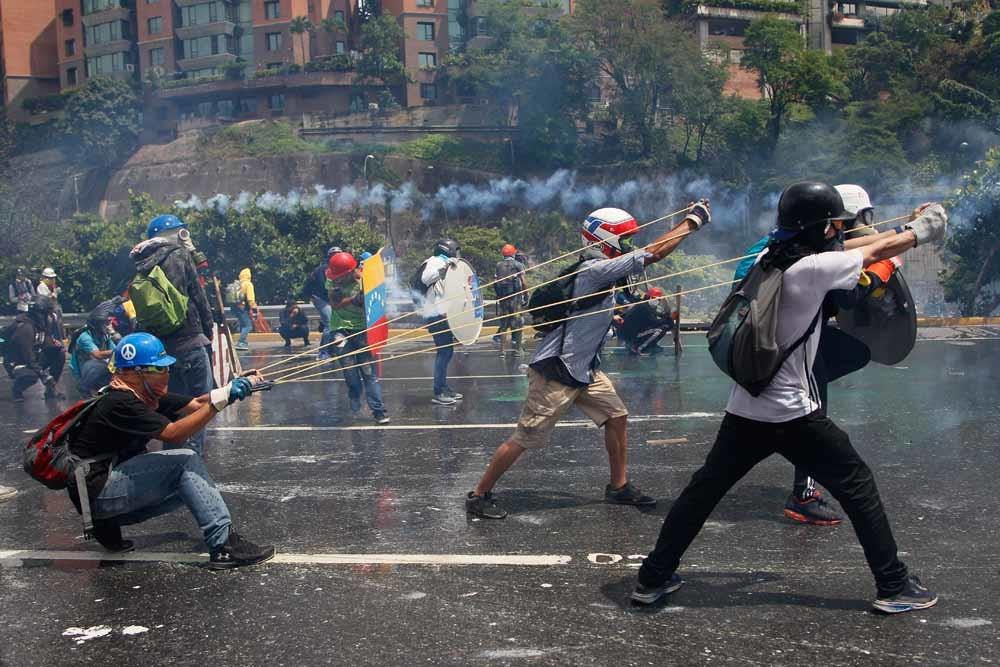 Met gigantische katapulten schieten demonstranten flessen met fecaliën naar de strijdkrachten die de weg naar het (pro-Maduro) Hooggerechtshof blokkeren. – © Ariana Cubillos / HH