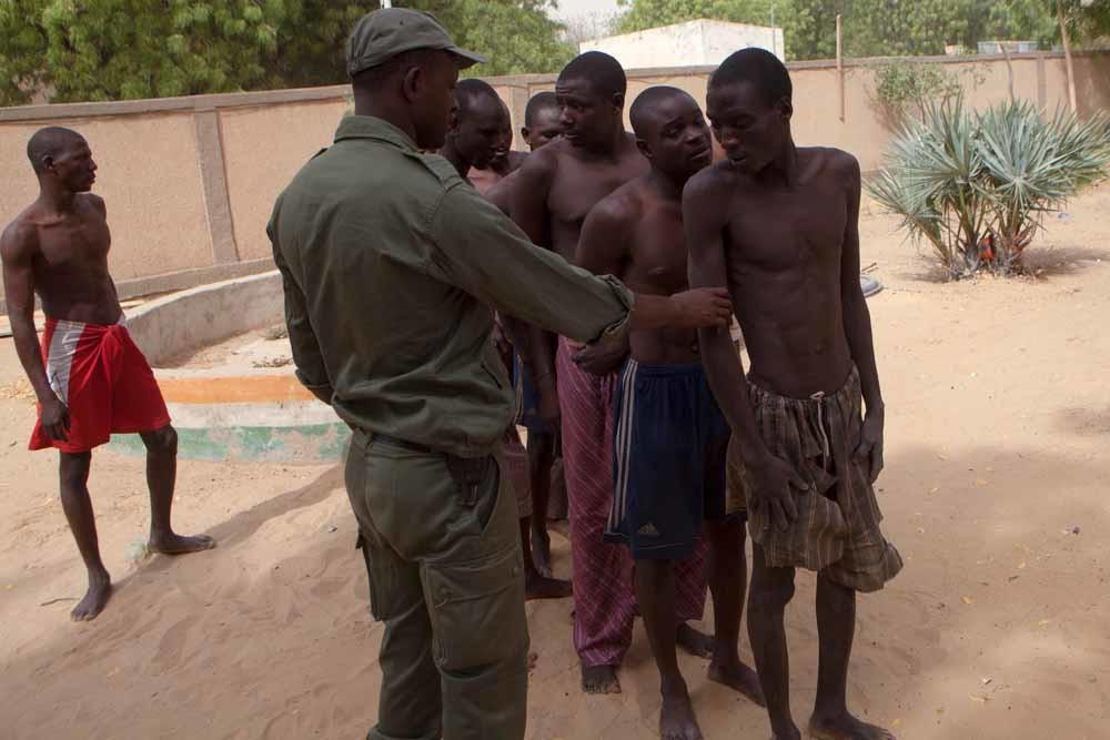Een Nigeriaanse soldaat met vermoedelijke leden van Boko Haram op de grens van Nigeria en Niger. – © Getty