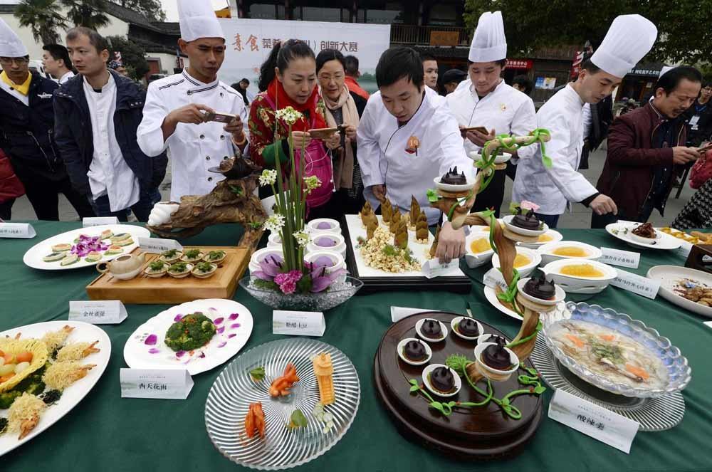 Chefs presenteren hun gerechten tijdens een vegetarische kookwedstrijd in Hangzhou. –  © Xinhua News Agency