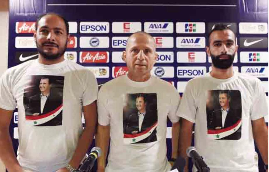 De Syrische coach Fajer Ebrahim (m.) draagt een T-shirt met de a eelding van Assad voor de match tegen Singapore in november 2015. – © Roslan Rahman / AFP /Getty Images
