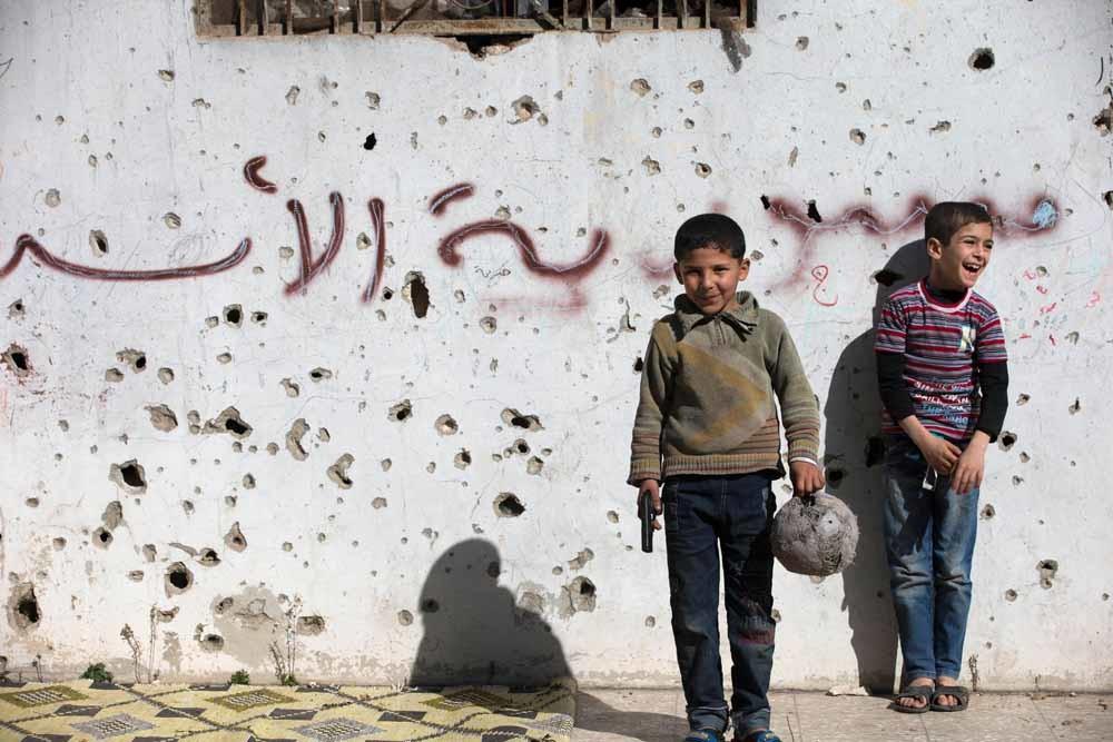 Een Syrische jongen houdt een speelgoedpistool vast tijdens een partijtje voetbal in de kapotgeschoten oude stad van Holms. – © Hassan Ammar / HH