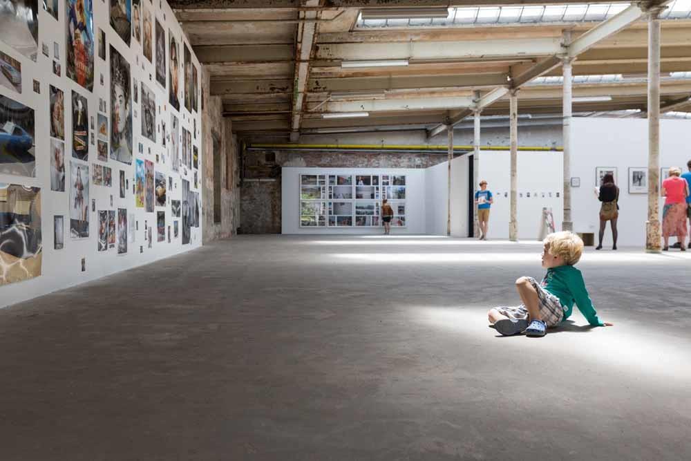 Een jongetje op een fototentoonstelling in een oude fabriek. – © HH