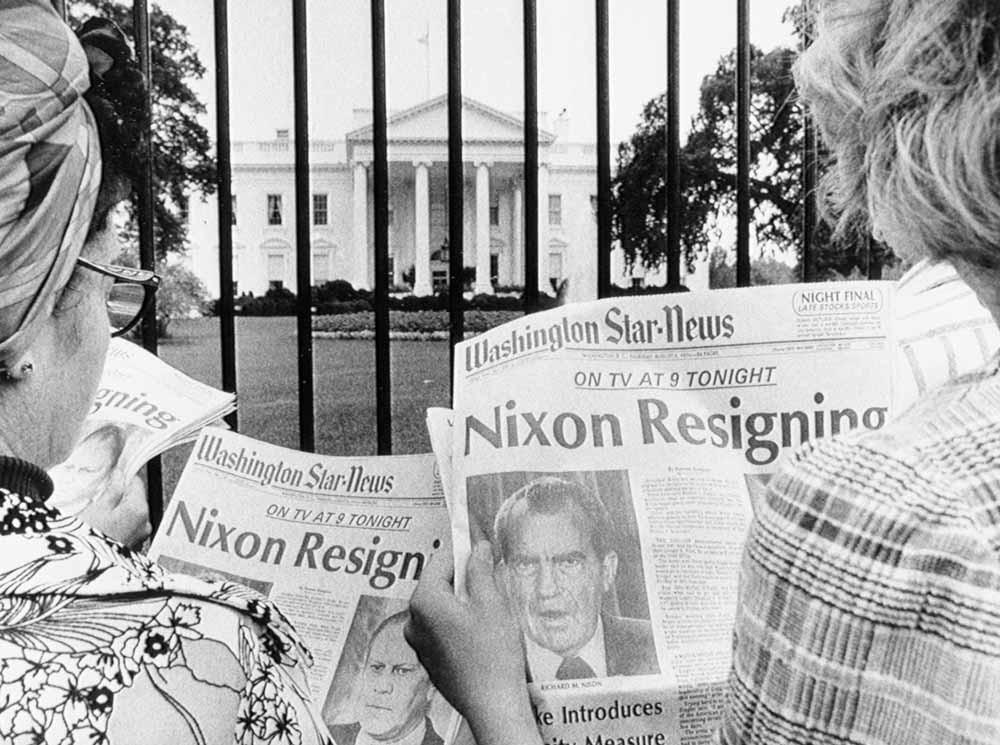 Toeristen bij het Witte Huis lezen het nieuws over het aftreden van de president. – © Getty