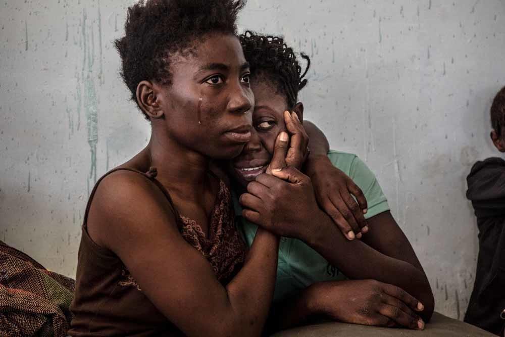 Met deze foto, 'The Libyan Migrant Trap', won fotograaf Daniel Etter een derde prijs bij de World Press Photo 2016. De foto toont twee Nigeriaanse vluchtelingen in een detentiecentrum in het Libische Sorman. – © Daniel Etter/World Press Photo/HH