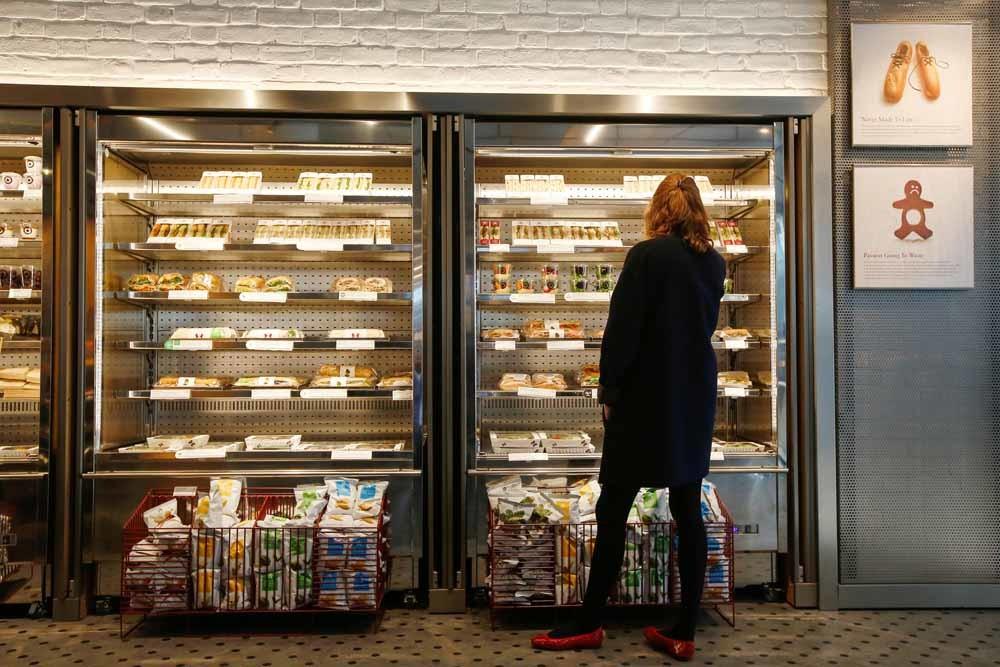 Een klant bekijkt het aanbod van Pret a Manger in een filiaal in Londen. – © Luke MacGregor / Getty