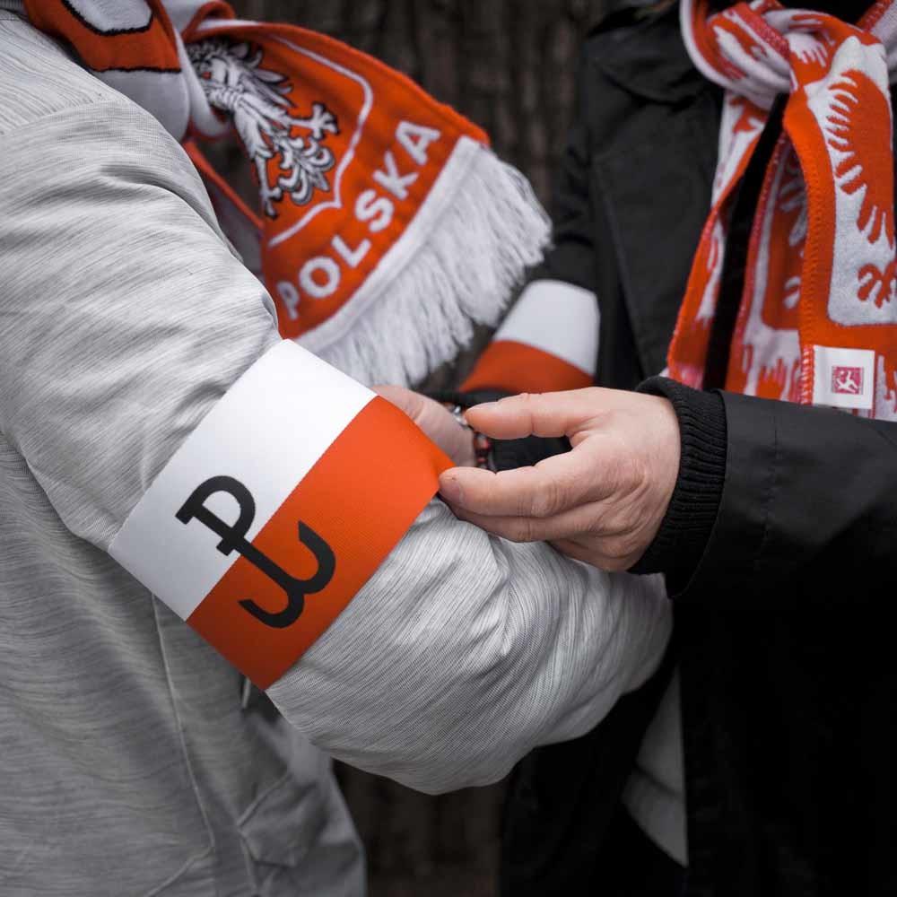 Aanhangers van regeringspartij PiS doen armbanden om bij een demonstratie. – © HH