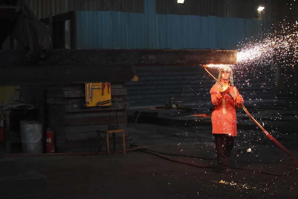 Een Amerikaanse staalarbeider snijdt een nieuw-gegoten plaat staal af in een fabriek in Indiana. – Scott Olson / Getty Images