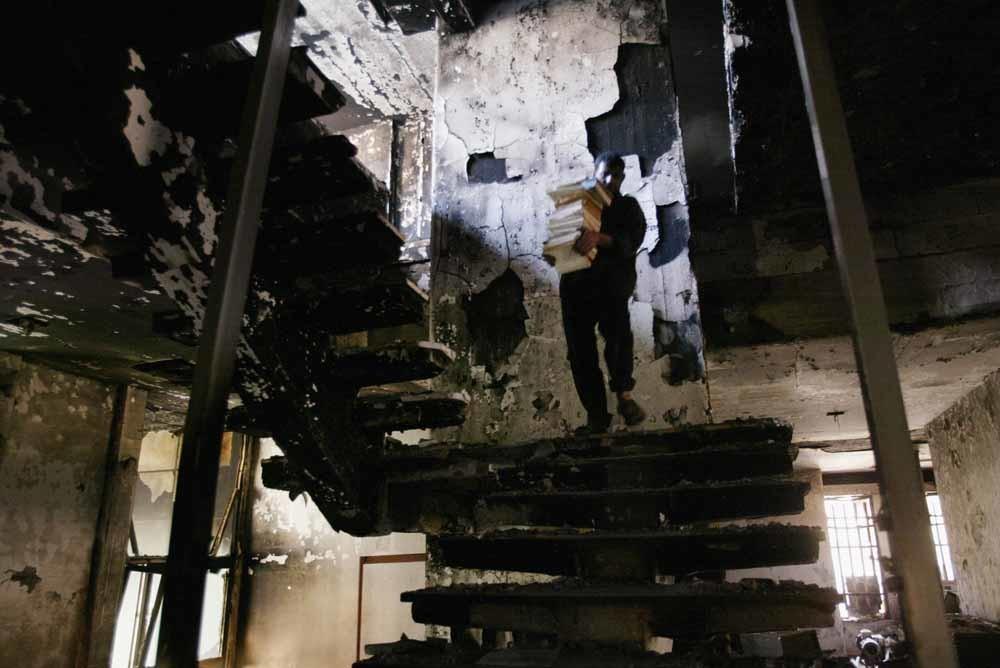 Een Iraaks man redt een stapel boeken uit de verwoeste Nationale Bibliotheek in 2003. – © Oleg Nikishin / Getty Images