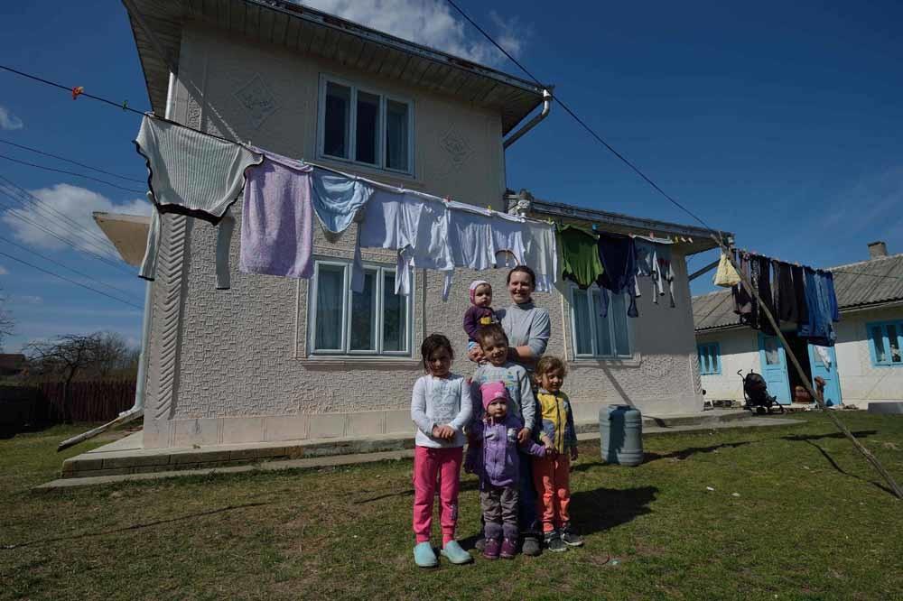 Nieuwe bewoonster Valentina Sotir (42) met vijf van haar acht kinderen voor hun huis in Concesti. Valentina is een alleenstaande moeder die slachtoffer werd van huiselijk geweld. Voor haar was Concesti een uitkomst. – © Daniel Mihailescu / AFP / Getty