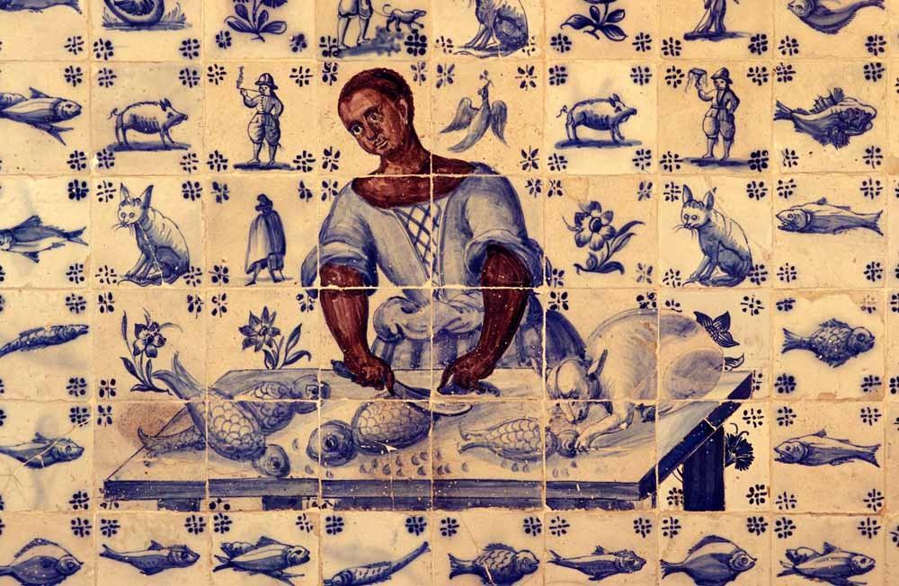 Een tegelafbeelding van een kokende slaaf in het stadsmuseum van Lissabon. – © Maurizio Borgese / HH