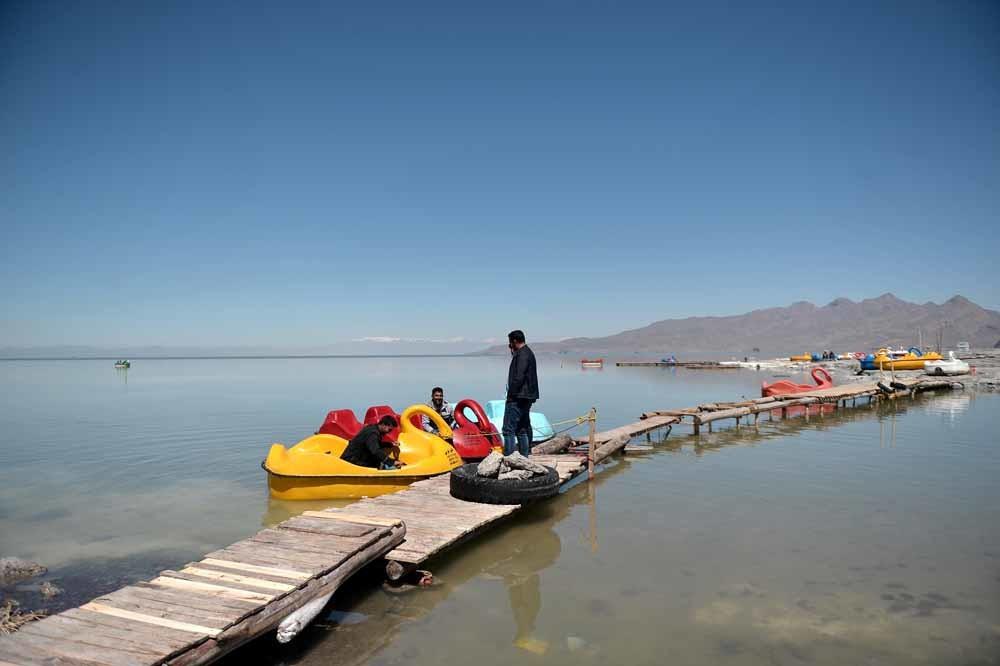 Toeristen op waterfietsen in het Oermiameer in Iran. Het grootste meer in het Midden-Oosten dreigt volledig op te drogen. – © Getty Images