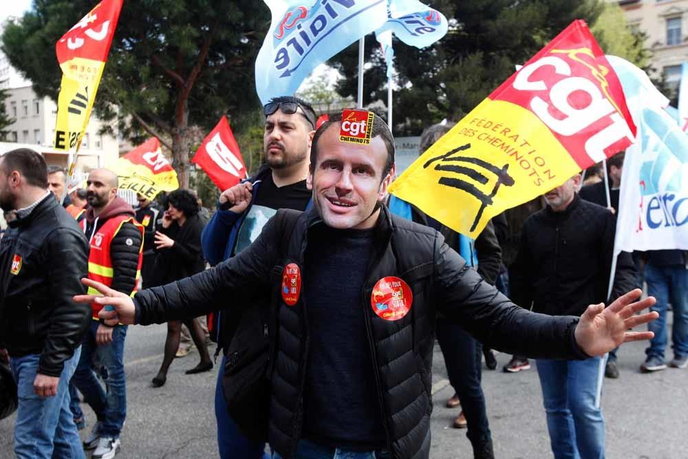 Een stakende spoorwegarbeider met een masker van Macron tijdens een betoging in Marseille op 13 april. – © Claude Paris / HH