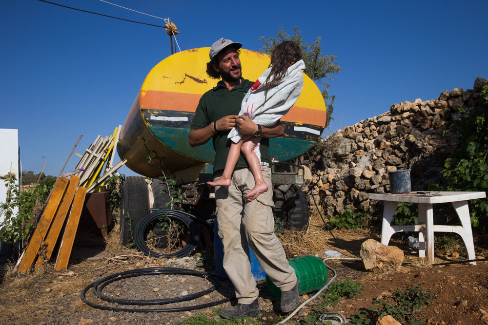 Ali Abu Awwad met zijn dochter, die net een douche heeft genomen uit de watertank in zijn tuin. – © Nati Shohat / HH