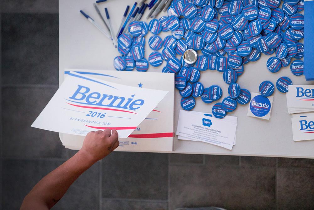 Een aanhanger van Sanders pakt een verkiezingsplakkaat op een bijeenkomst in de Valley High School in West Des Moines, Iowa. – © Scott Olson / Getty Images