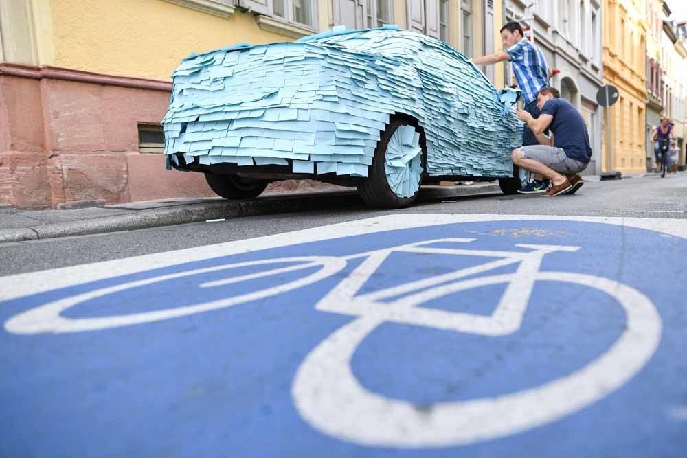 Mannen plakken post-its op een foutgeparkeerde auto in Heidelberg in 2016. Ze vroegen hiermee aandacht voor het vrijhouden van  etspaden. – © Uwe Anspach / AFP / Getty Image