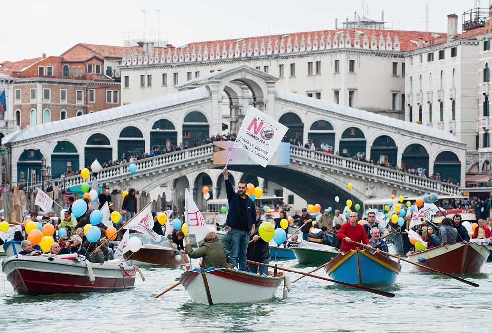 Venetianen verzamelen zich op bootjes bij de Rialtobrug als protest tegen het groeiende aantal cruiseschepen in de stad. – © Getty