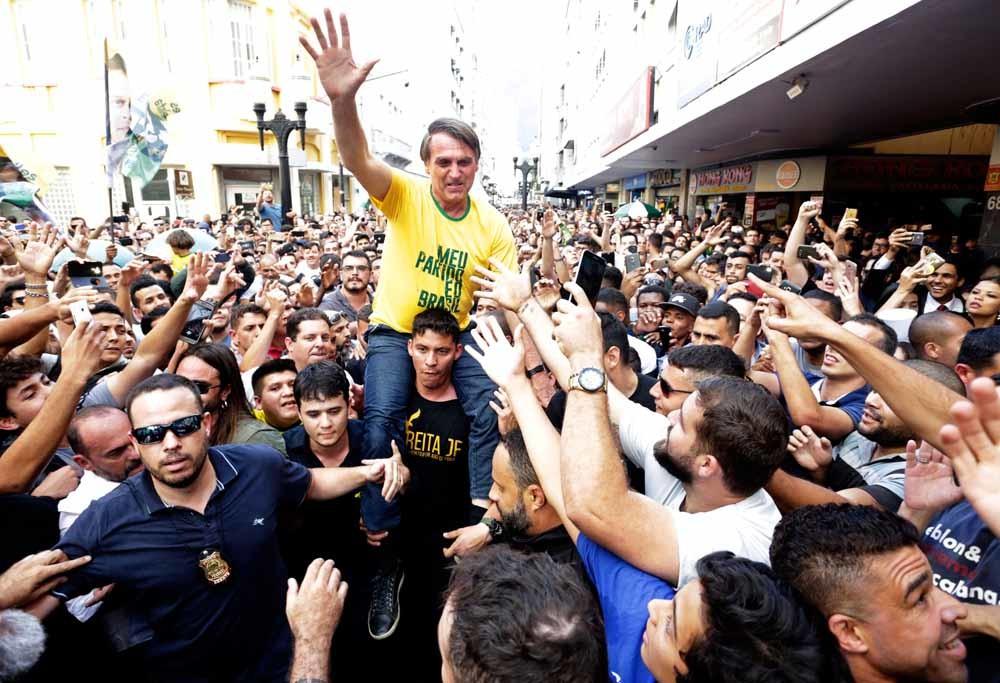 Fans dragen Jair Bolsonaro tijdens zijn campagne in Juiz de Fora op de schouders. Enkele momenten later wordt hij aangevallen met een mes. – © Antonio Scorza/Agencia O Globo via AP