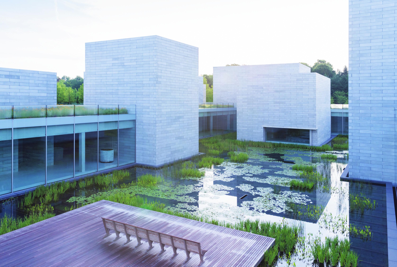 De Pavilions, de uitbreiding van Glenstone, bestaat uit onderling verbonden galeries, gegroepeerd rond een bassin, gelegen op een zacht glooiende heuvel. – © Glenstone, Iwan Baan