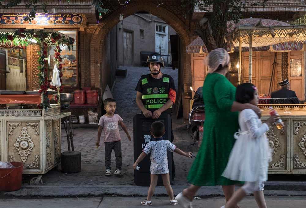 Oeigoerse kinderen dollen met een politieagent in Kashgar, een van de laatste steden in Xinjiang waar nog traditionele Oeigoerse cultuur te vinden is. – © Getty Images