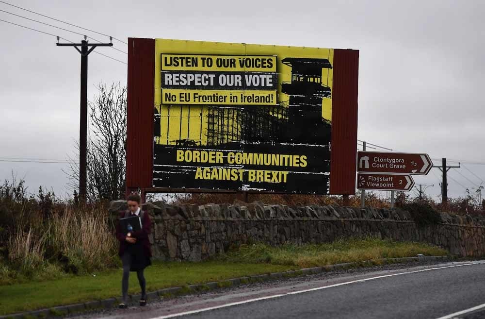 In Noord-Ierland loopt een student langs een anti-Brexit-billboard. De grens tussen de Republiek Ierland en Noord-Ierland is een heet hangijzer in de onderhandelingen. – © Getty Images