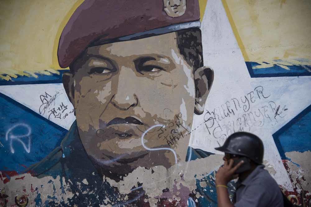 Een voorbijganger belt terwijl hij langs een muurschildering van president Maduro loopt, op zich niks bijzonders maar in Venezuela wel omdat de netwerken worden aangevallen in een poging de overheid te verzwakken. © Getty