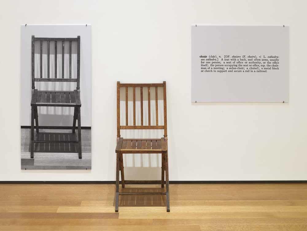 Het gedachte-experiment One and Three Chairs (1965) van de Amerikaanse kunstenaar Joseph Kosuth. Gewoon een stoel, geflankeerd door een foto van diezelfde stoel en aan de andere kant een woordenboekdefinitie van het woord stoel. Joseph Kosuth. – © Aeon