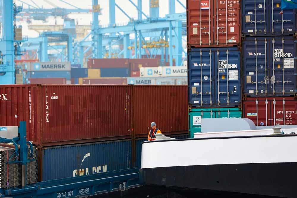 Een vrachtschip met containers wordt de haven van Rotterdam binnengeloodst. – © Getty Images