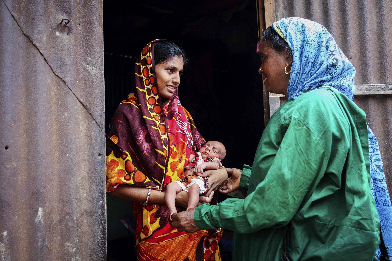 Vroedvrouw Laili Khatun bezoekt Rabeya (18) en haar dochter Lamia, van vijftien dagen oud. – © Jaco Klamer. Panos Pictures