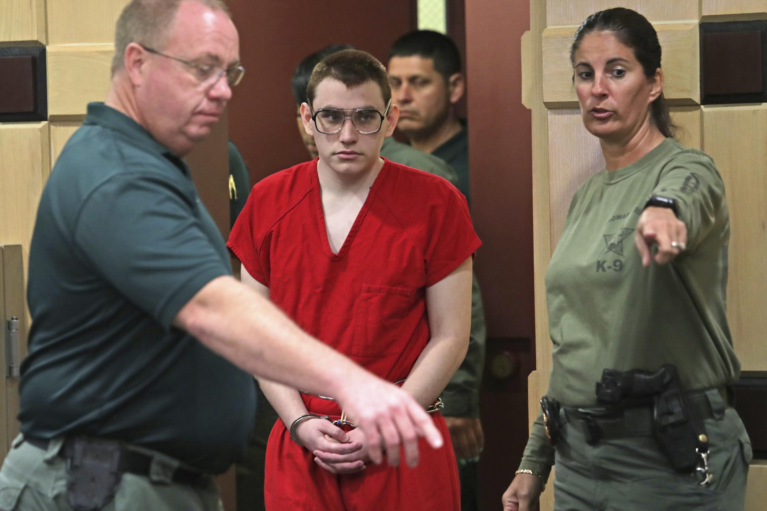 Nikolas Cruz wordt de rechtszaal in begeleid voor een zitting over de vraag of hij onder toezicht moet blijven staan van een officier die hem naar zijn zeggen mishandeld heeft. – John McCall / South Florida Sun-Sentinel via AP / HH