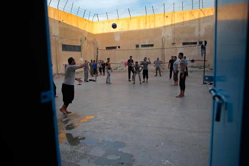 Voormalige IS-strijders spelen volleybal in een Koerdische gevangenis in Noord-Syrië. – © AP Photo / Hussein Malla