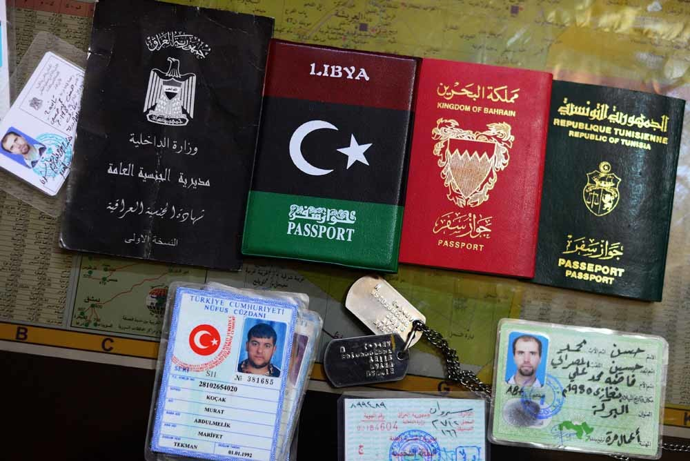 De identiteitsbewijzen van buitenlandse IS-strijders uit Irak, Libië, Bahrein, Tunesië en Turkije die via Turkije naar Syrië zijn gereisd. – © HH
