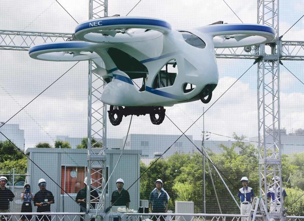 Het Japanse elektronicabedrijf NEC Corporation geeft een demonstratie van zijn 'vliegende auto', een op een drone lijkende driewieler met vier propellers. – © Koji Sasahara / AP Photo NEC