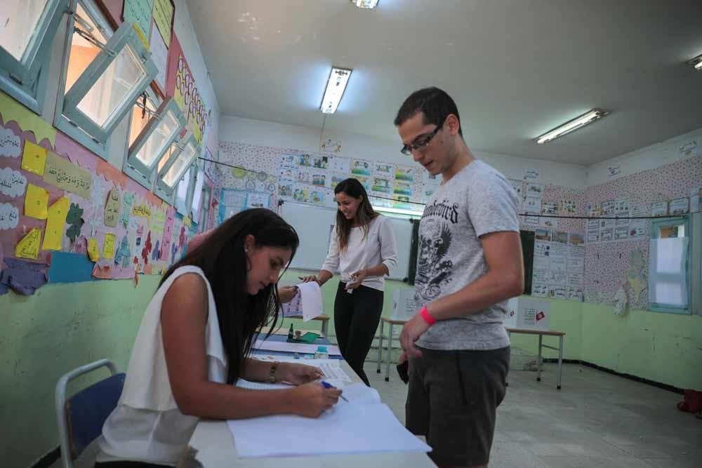 Jonge Tunisiërs in een stemlokaal in Tunis tijdens de eerste ronde van de presidentsverkiezinging in Tunesië. – © Mosa'ab Elshamy / AP Photo
