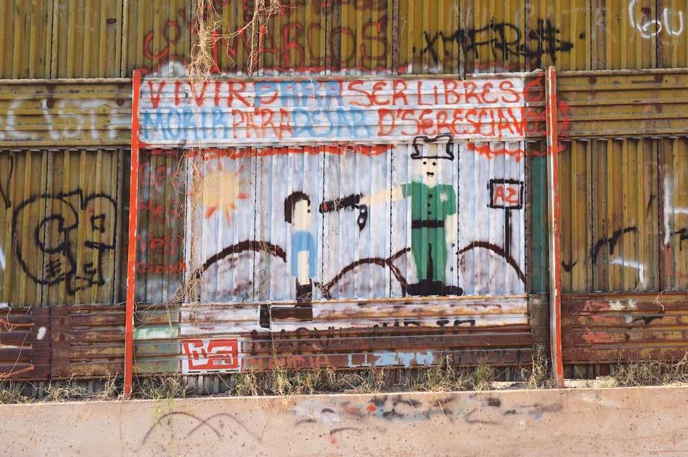 Graffiti aan de Mexicaanse kant van de grens tussen de VS en Mexico. Elke dag steken zo'n tweeduizend migranten deze grens over op de vlucht voor geweld of vervolging in hun thuisland.  © Christopher Morris / Corbis / Getty Graffiti
