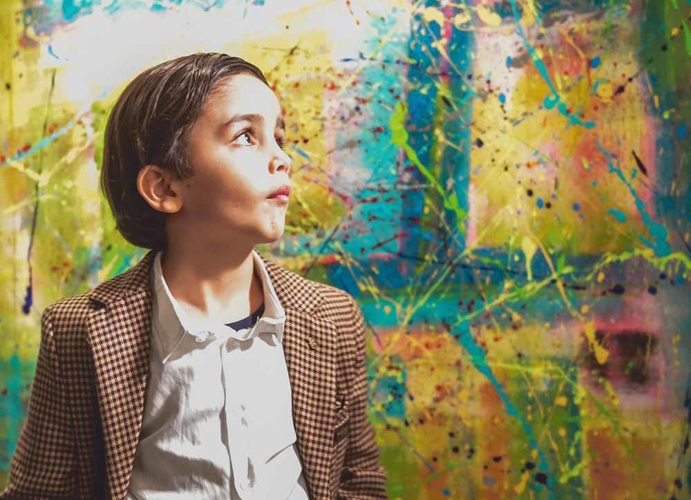 De zevenjarige Mikail Akar voor een van zijn schilderijen in een galerie in Hamburg. – © Axel Heimken / Newscom