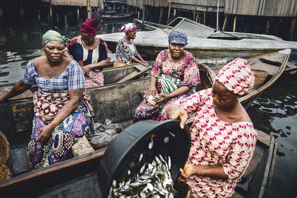 Vissersvrouwen onderhandelen met inkopers in Makoko, een gemeenschap aan de Lagos Lagoon die dreigt te worden ontruimd.© Jesco Denzel / HH
