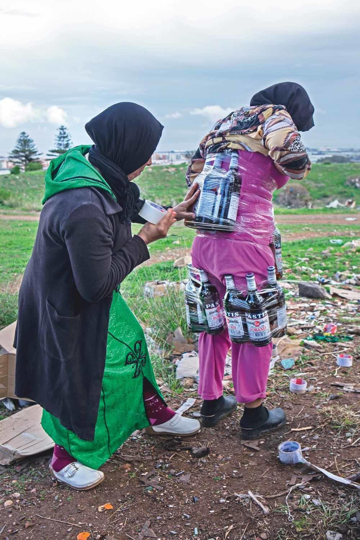 Een vrouw laat flessen pastis aan zich vasttapen waarmee ze de Spaans-Marokkaanse grens gaat oversteken. © Ana Nance / Redux / HH