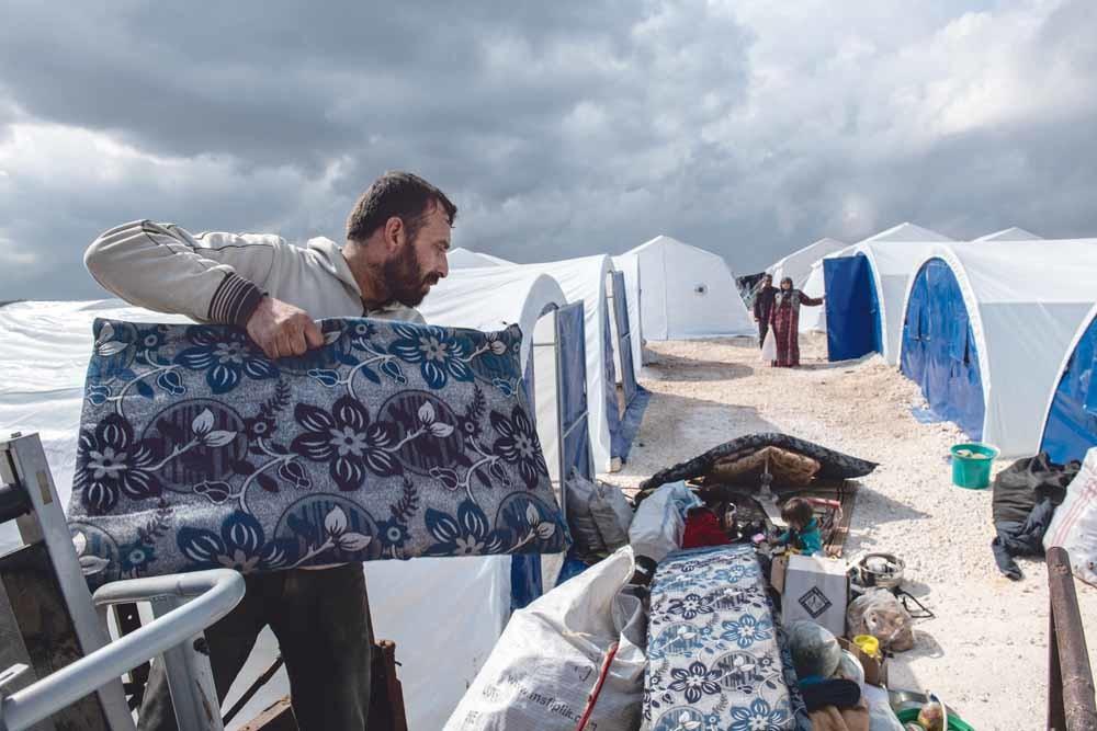 Een Syrische man laadt de bezittingen van zijn familie uit een laadbak in een nieuw ingericht vluchtelingenkamp in de buurt van Atmeh, in de provincie Idlib.  © Burak Kara / Getty Images