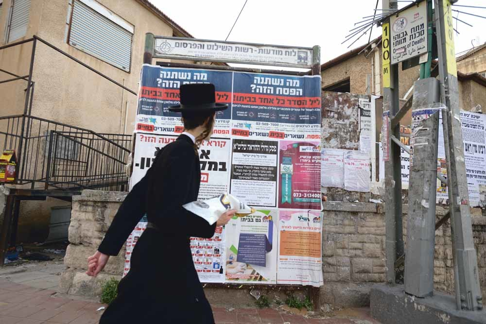 In de ultraorthodox-joodse stad Bnei Brak in Israël loopt een jongen langs aanplakbiljetten die bewoners manen om thuis te blijven tijdens Pesach, dat van 8 tot 16 april gevierd werd. – © Gili Yaari / NurPhoto/ Getty Images