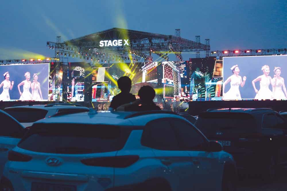 Publiek kijkt vanuit de auto naar een optreden tijdens het muziekfestival Stage X, op 25 mei. Meer dan duizend mensen waren aanwezig bij dit 'social-distance-evenement' op een parkeerplaats in een buitenwijk van Seoul. – Ahn Young-joo / AP