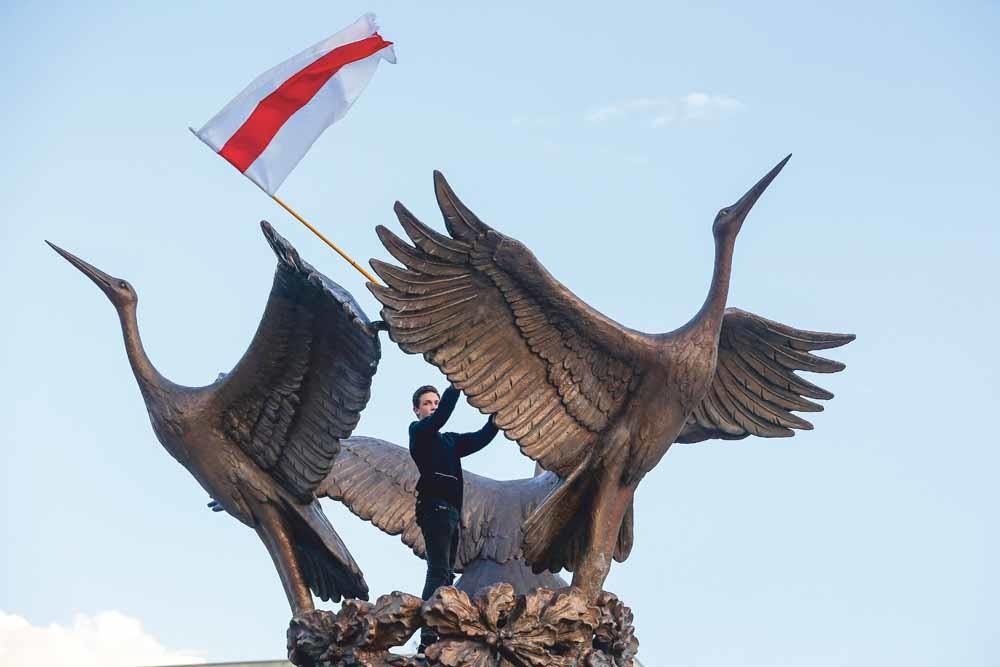 De onofficiële vlag van Belarus uit 1918 wappert op een monument van drie zwanen tijdens een demonstratie tegenover het overheidsgebouw in Minsk. © Sergei Grits /AP