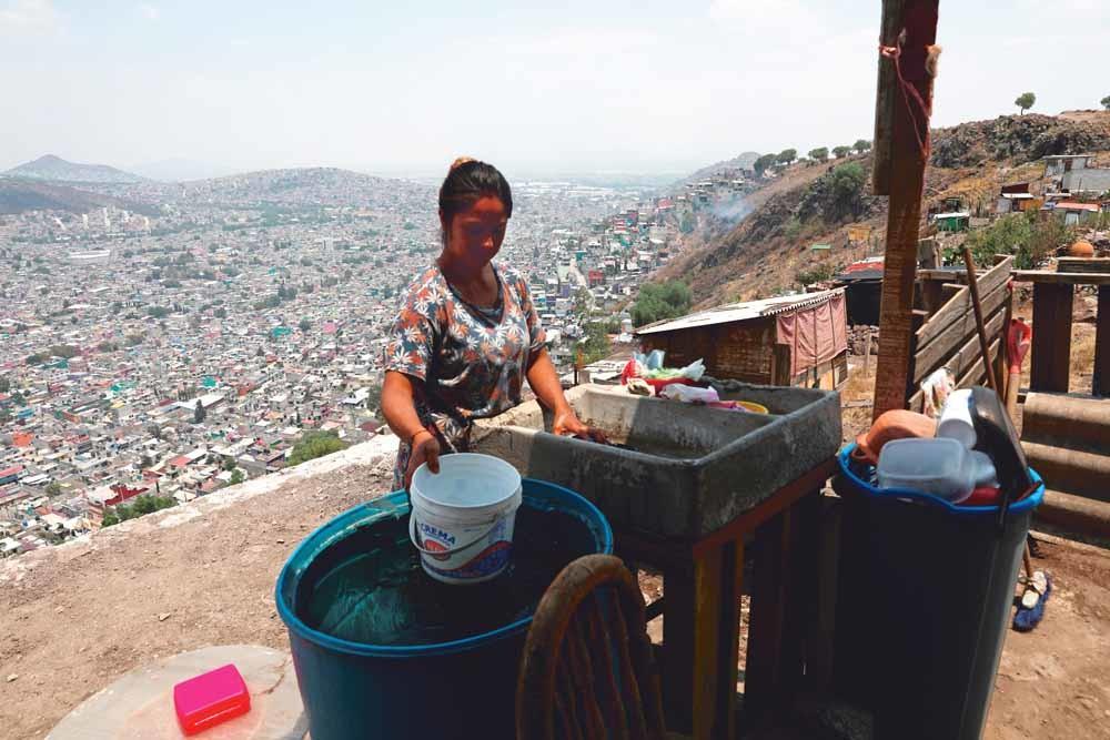 Een vrouw in Ecatepec haalt water bij la pipa, een tankwagen die water distribueert in wijken waar dat niet of nauwelijks aanwezig is. – © Reuters / Henry Romero