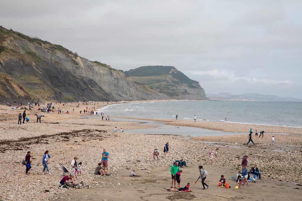 Toeristen en amateur-geologen zoeken naar fossielen op Charmouth Beach in Zuid-Engeland. Deze zogenaamde Jurassic Coast staat op de Werelderfgoedlijst en ligt aan het Kanaal. – © Mike Kemp / In Pictures / Getty