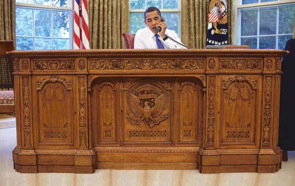 President Barack Obama voert in 2009 een telefoongesprek vanachter de Resolute Desk. – © Pete Souza